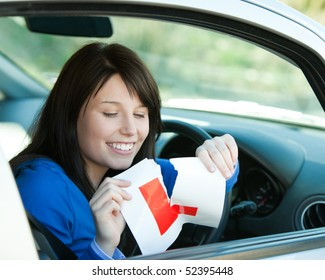 Brunette teen girl sitting in her car tearing a L-sign after having her driver's licence