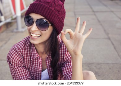 Brunette teenage girl in hipster outfit (jeans shorts, gumshoes, plaid shirt, hat) with a skateboard at the park outdoors.