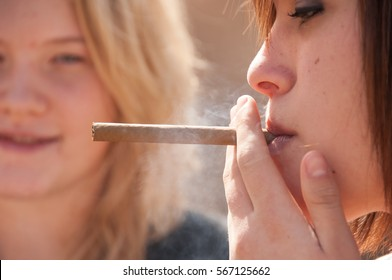 Brunette teenage girl takes a drag of a thin cigar, blonde girl friend watches, out of focus.  Shallow depth of field, focus on woman in the foreground smoking cigar.