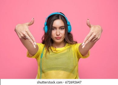 Brunette teenage girl wearing yellow sheer shirt and headphones making gesture against pink background.