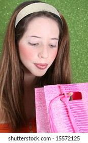 Brunette teenager peeping into a pink gift bag