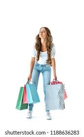 brunette tired girl holding heavy shopping bags, isolated on white