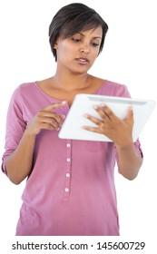 Brunette using her tablet pc on white background