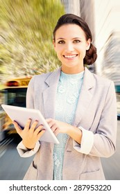 Brunette using tablet pc against school bus in city