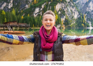 A brunette wearing outdoor gear is laughing and smiling while taking selfie. She is on the shores of Lake Bries. Behind her, wooden boats, a rustic pier, and golden and green trees reflect the autumn.