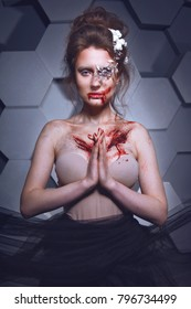 Brunette with white flowers in her hairstyle and with bloody scars on her chest on red background