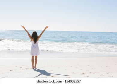 Brunette in white sun dress standing by the water with arms raised on the beach