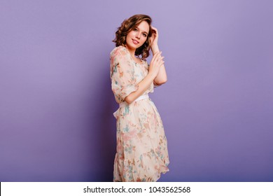 Brunette winsome woman in long light dress looking with interest to camera and smiling. Chilling girl with short hairstyle standing in room on purple background.