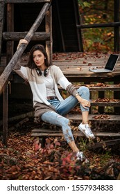 A brunette, with wireless headphones, dressed in ripped jeans and brownish knitwear, is sitting on wooden stairs in front of a cabin in autumn