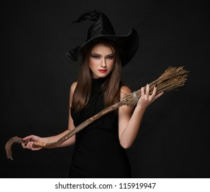 The  brunette witch with a broom in a black dress in the studio