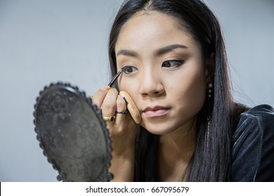 Brunette woman applying make up and applying liquid eyeliner with brush, close up