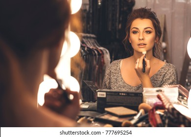 Brunette woman applying make up (paint her skin) for a evening date in front of a mirror. Focus on her reflection