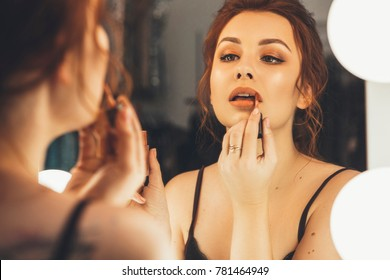 Brunette woman applying make up (paint her lips) for a evening date in front of a mirror. Focus on her reflection