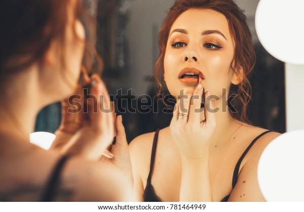 鏡の前で夕方のデートに化粧(唇を描く)をするブルネットの女性。彼女の反省に集中する