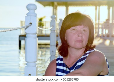 brunette woman of average years striped dress at sunset on the seashore