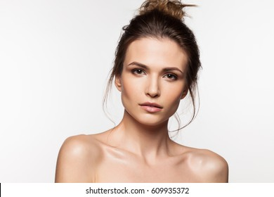 Brunette woman with bare shoulders, with clean skin and natural make-up on a white background