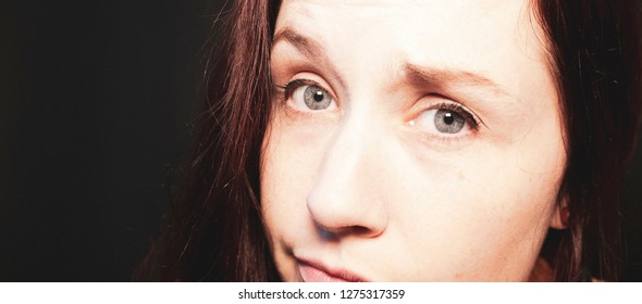 Brunette woman with blue eyes making a skeptical expression with a black background.