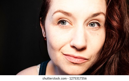 Brunette woman with blue eyes smiling and looking to the side of the camera with a black background.