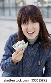 Brunette woman in blue jacket with money in her hands outside