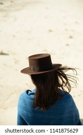 Brunette woman in brown hat and blue cloth standing in windy desert. Rear view.