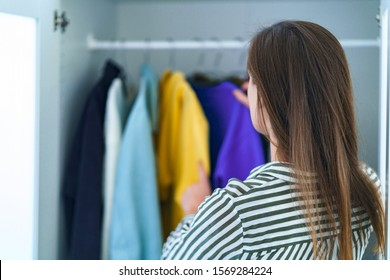 Brunette woman choosing outfit from wardrobe closet with stylish clothes and home stuff