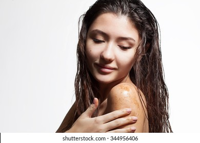 Brunette woman cleans the skin of the body coffee scrub on a white background isolated