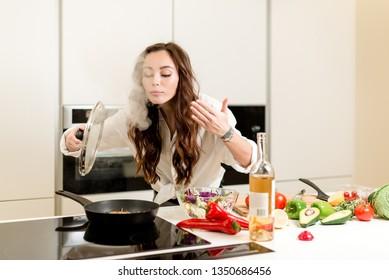 Brunette Frau kocht frisches Fischsteak und duftenden Dampf in der Küche mit Gemüse und Glas Weißwein. Hausfrau-Konzept