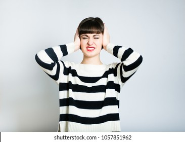 Brunette woman covering her ears with both hands :I can't hear!