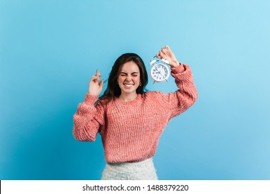 Brunette woman crossed her fingers and holds white alarm clock. Model in oversize sweater posing on blue background