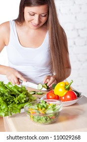 brunette woman cutting  fresh cucumber for salad over white brick wall