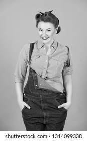 Brunette woman in denim on gray background. Girl with curls and head scarf in retro american worker style. Woman model isolated in studio. Happy woman in denim