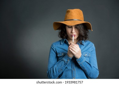 Brunette woman with denim shirt and cowboy hat, smoking a cigarette with serious expression, isolated on gray background