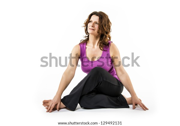 Brunette woman is doing a stretching exercise on white background