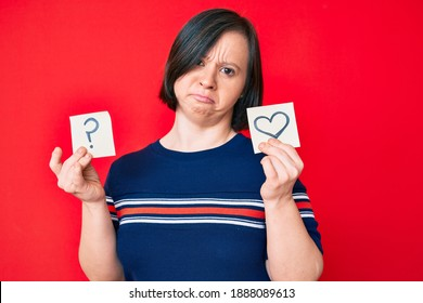 Brunette woman with down syndrome holding heart and question mark reminder relaxed with serious expression on face. simple and natural looking at the camera.