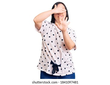 Brunette woman with down syndrome wearing casual clothes covering eyes with hands and doing stop gesture with sad and fear expression. embarrassed and negative concept.