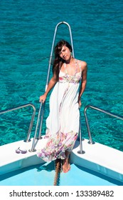 Brunette woman in dress standing on bow of yacht and looking at camera