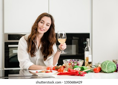 Brunette woman drinking glass of white wine at home in the kitchen with fresh vegetables and fish steak