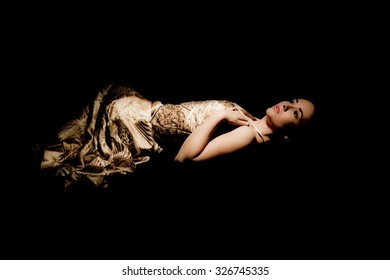 brunette woman in evening gown lying down on black background