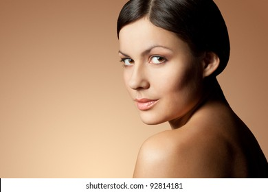 brunette woman face and shoulder over skintone background