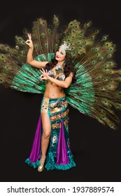 Brunette woman with feathers her head against the background of lush peacock feathers.