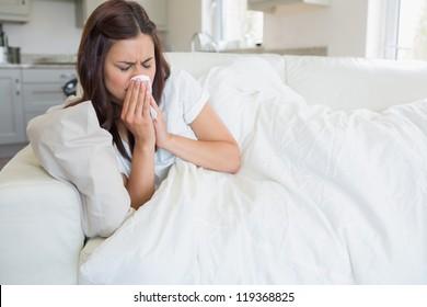 Brunette woman feeling ill on sofa