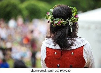 A brunette woman with a flower wreath on her head is celebrating midsummer in Sweden. Seen from behind.