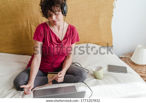 brunette woman in front of her laptop sitting on the bed, listening and dancing with headphones some music, buying with credit card, online shopping concept in comfort at home