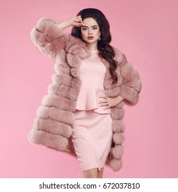 Brunette Woman in fur coat over pink. fashion studio photo of gorgeous sensual woman with long wavy hair in luxurious dress