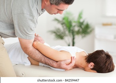Brunette woman getting a shoulder-stretching in a room