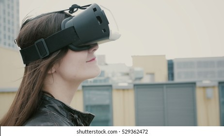 Brunette woman girl with waving hair uses a virtual reality glasses on the roof. 4k