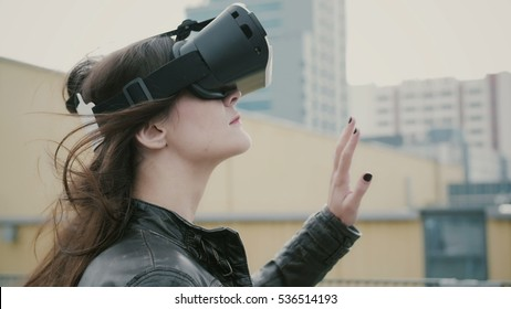 Brunette woman girl with waving hair uses 3D Virtual Reality headset on the roof. 4k