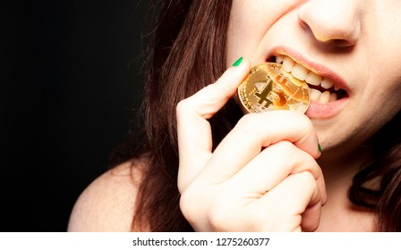 Brunette woman with green nails biting a golden Bitcoin coin and a black background.