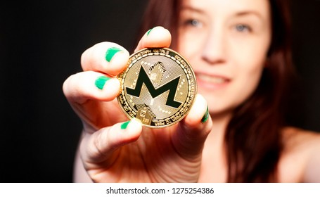 Brunette woman with green nails holding a golden Monero coin with a black background
