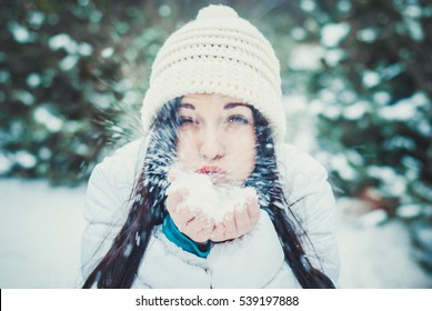 brunette woman is happy and blowing snow in the winter nature